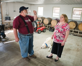 by: Chase Allgood, R.J. and Juanita Lint sample wine while Ghost, the vineyard dog, enjoys the cool concrete floor of the barrel room.