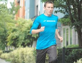 by: David Ball, Centennial High graduate Ryan Vail takes a few warm-ups passes in front of his apartment in the St. John's area. He puts in 120 miles a week as a professional runner – most of those coming on the trails of Forest Park.