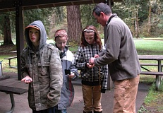 by: ESTACADA NEWS ISABEL GAUTSCHI - Jeff Livick of Timberline Ski Patrol teaches Austin Roberts, Alexandra Evrard and Alayna Roberts of the Mossy Rocks 4-H club compass skills.