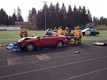 by: COURTESY OF TVF&R - Emergency personnel wheel out a victim of a mock traffic collision involving a drunk student driver.