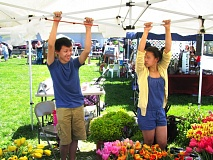 by: NEWS PHOTO: STEVEN BROWN - Keane Xiong, 15, and his sister, Holly, 15, (they arent twins) hold down the pop-up canopy that was at risk of blowing away Saturday, May 4, at the Estacada Farmers Market.