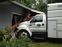 by: SUBMITTED - A truck slammed into a home on Fernwood Circle Wednesday morning. It's unclear how that happened; a tree-care workers in charge of the vehicle said the brake was set and the wheels were blocked.