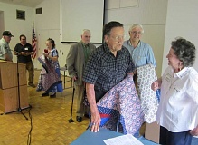 by: BARBARA SHERMAN - UNEXPECTED GIFTS - After receiving patriotic quilts from Elisabeth Hampton (in background holding quilt), veterans line up to register with host Billie Reynolds.