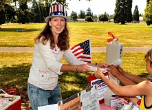 by: DAVID F. ASHTON - Volunteer event organizer, and neighborhood association board member, Kendall Palmer serves ice cream at Brentwood-Darlingtons first Independence Day event.