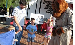 Photo Credit: GAZETTE PHOTO: RAY PITZ - Josiah Kelley, 5, of Sherwood, center, says hello to McGruff the Crime Dog during Sherwood's National Night Out held Aug. 5. at Sherwood's Cannery Square Plaza.