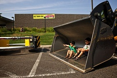 Photo Credit: TIMES PHOTO: JAIME VALDEZ - Aarman Patel, 2, and his older brother, Aashir, 4, pose for a picture in the shovel of a bulldozer for their parents at Big Truck Day on Saturday at the Conestoga Recreation and Aquatic Center.