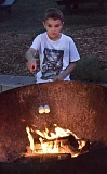 Photo Credit: TIDINGS PHOTOS: VERN UYETAKE - West Linn's Liam Krubel roasts marshmallows at the Great Outdoor Adventure Aug. 16.