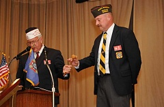 Photo Credit: REVIEW PHOTO: VERN UYETAKE - Ken Kraft (right) receives the gavel symbolizing the beginning of his service as post commander for the new VFW post in Lake Oswego. Presenting the gavel is past state VFW commander Jason Carol.