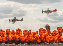 Photo Credit: TOM BROWN - A German Focke-Wulf 190 is trailed by a P-51 Mustang above Homeland Fireworks' Wall of Fire on Saturday, after a re-creation of a World War II aerial dogfight for the enjoyment of attendees at the 15th annual Airshow of the Cascades. The two-day event drew about 16,000 people and about 150 aircraft.