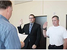 Photo Credit: HOLLY M. GILL - Madras City Administrator Gus Burril, left, swears in two new reserve officers for the Madras Police Department, Isiah Duarte and Bud Stout, right.