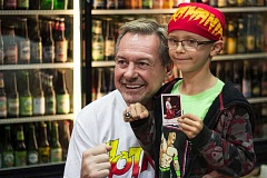 Photo Credit: TIMES PHOTO: LACEY JACOBY - Elijah Fenner, 8, of Portland poses with Rowdy Roddy Piper at Rocket Fizz soda shop on Saturday. Piper posed for pictures and signed bottles of his new Rowdy Roddy Pipers All Out Of Bubblegum flavored soda.
