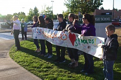 Photo Credit: CONTRIBUTED PHOTO: DARLYN CHESTER - Community members rallied with banners, signs and balloons to welcome back Reynolds High School students Friday.