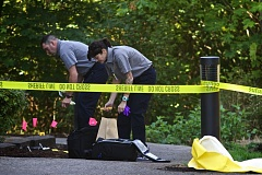 Photo Credit: TIMES PHOTO: JAIME VALDEZ - Members of the Oregon State Forensics team pack up gear after performing their duties at the scene of a homicide at the Birch Pointe Apartments in Beaverton.