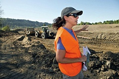 Photo Credit: TRIBUNE PHOTO: JAIME VALDEZ -  Julie Mentzer, director of environmental operations for Wildlands Inc. in Portland, explains how earth movers are reshaping the terrain on the southern tip of Sauvie Island, enabling wildlife to travel back and forth from the Willamette River and Multnomah Channel to future woodlands that will be planted with oak and cottonwood trees.