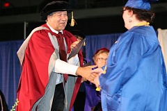 Photo Credit: SUBMITTED PHOTO: PCC - Portland Community College President Jeremy Brown hands out diplomas on stage at the Memorial Coliseum during the college's commencement in June.