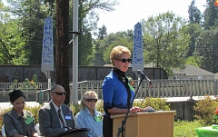 Photo Credit: MARK MILLER - Julie Vigeland, chairwoman of the Oregon Arts Commission, speaks at the ribbon-cutting ceremony for the St. Helens Gateway Sculpture Project. The two 16-foot-tall, obelisk-shaped lanterns created for the project are visible in the background, on the other side of Highway 30. Also pictured, from left to right: project director Kannikar Petersen, St. Helens Mayor Randy Peterson and project artist Suzanne Lee.