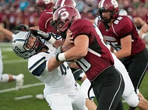Photo Credit: SPOKESMAN PHOTO: JOSH KULLA - Wilsonville's Austin Warr gets a stiff arm from Sandy runner Calvin McKinnis in the Pioneers' 7-6 3OT win Friday.