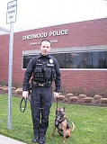 Photo Credit: GAZETTE FILE PHOTO - Irma, a Belgian Malinois, and her handler, Officer Corey Jentzsch, stand outside the Sherwood Police Department when the K9 first joined the department. On Sept. 16, the Sherwood Police Foundation donated a ballastic vest to the K9 to keep her safe.