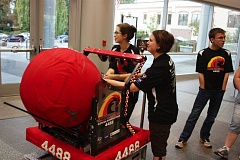Photo Credit: HILLSBORO TRIBUNE PHOTO: DOUG BURKHARDT - The Glencoe High School robotics team demonstrates how the robot they designed can throw a ball. Team members brought their robot to the Hillsboro Civic Center for a demonstration in front of the city council.