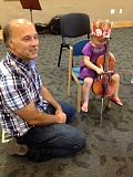 Photo Credit: COURTESY PHOTO - A young girl got the chance to play one of Oregon Symphony musician Ken Finchs mini cellos, a viola with an added point on the end.