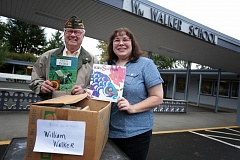 Photo Credit: TIMES PHOTO: JONATHAN HOUSE - Robert Thornhill and William Walker Elementary School secretary hold up some of the donated books for the after-school SHINE program.