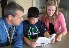 Photo Credit: COURTESY OF THE BETA BETA CHAPTER OF DELTA KAPPA GAMMA - Edy Ridge Elementary Principal Frank Luzaich and third-grade teacher Tori Hamachek watch Tristan Kieser read his new dictionary.