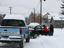 Photo Credit: JASON CHANEY - Local drivers work to free a car from a snowbank on Friday morning. According to local authorities, many drivers got stuck in the snow that day.