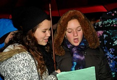 Photo Credit: REVIEW PHOTOS: VERN UYETAKE - Lake Oswego High School choir members Carolyn Miller (left) and Julia Wolf sing holiday favorites before the lighting Friday of Lake Oswegos holiday tree in Bigelow Plaza.