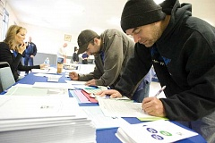 Photo Credit: KEVIN SPERL - Former Woodgrain Millwork employees Philip Gatto, right, and Michael Gatto, both cut shop graders, fill out applications at the Worksource Oregon booth at a job fair at Carey Foster Hall on Thursday.