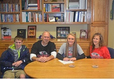 Photo Credit: HERALD PHOTO: COREY BUCHANAN - KaeLynn Miller signs her letter of intent with her family by her side.