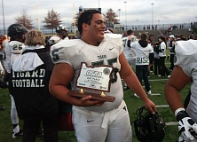 Photo Credit: DAN BROOD - TROPHY TIME -- Tigard High School senior lineman Kevin Henderson smiles as he holds the second-place trophy following Saturday's Class 6A state championship game at Hillsboro Stadium.