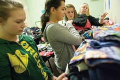 Photo Credit: KEVIN SPERL - Crook County Middle School seventh-grade teacher Cally Modin, far right, supervises her students (from right) Emily Eagan, Kaylie Foley, and Faith Lambdin as they help sort clothes in the schoo'ls Clothes Loft.