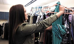 Photo Credit: PEGGY SAVAGE - Abby Rieskamp, an MHS junior, goes through her inventory of formals in the Clothes Closet at the school.