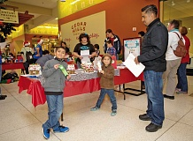 Photo Credit: CONTRIBUTED PHOTO: LAURA HINRICHS - Joshua Chavez, front from left, Ian Chavez and their father Emanuel Chavez took part in the Bonnie L. Hays Animal Shelters third-annual Gingerbread Dog House Contest on Saturday at Cedar Hills Crossing.
