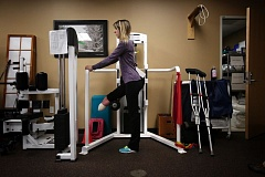 Photo Credit: TIMES PHOTO: JONATHAN HOUSE - Erica Bruns uses a lower leg maching as a strengthening exercise during a physical therapy visit to OHSU's Beaverton clinic.