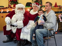 Photo Credit: HILLSBORO TRIBUNE PHOTO: CHASE ALLGOOD - Jeremy Davis calms his crying nephew, Collin Davis, as they visit Santa and Mrs. Claus. About 250 children attended the meet-and-greet Saturday, Dec. 13, in the Cornelius Public Library. Sponsored by the Cornelius Booster Club, the afternoon included activities and a photo of each child with Santa.