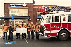 Photo Credit: CONTRIBUTED PHOTO - Gresham firefighters from Local 1062 presented SnowCap Community Charities Executive Director Judy Alley with a $1,062 donation toward the Fill-a-Bag food drive at Riverview Community Bank on Thursday, Dec. 18. Firefighters reached into their own pockets to raise the funds, which will be used to help fill the shelves at SnowCaps warehouse. Making the presentation were, left to right, Ryan Miller, SnowCap Executive Director Judy Alley, Anthony Foster, Mark Robison, Josh Butler, Firefighters Local 1062 President Kevin Larson, Ian Wynne and Joe Covey.