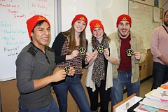 Photo Credit: POST PHOTO: KYLIE WRAY - Left to right, Hipolito Lopez-Hernandez, Bekah Mather, Lexie Moss and Peter Limbaugh receive patches from adviser Andy Wex at the Aquanauts Christmas party Dec. 17.