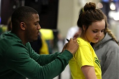 Brooklyn Petersen (right) gets an autograph on the back of her Oregon shirt from former Ducks star running back LaMichael James.