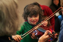 Photo Credit: CONNECTION PHOTO: KELSEY O'HALLORAN - Milo Baxter-Neal, 4, grins as he hears himself playing 'The ABCs' tune on a violin, guided by longtime Oregon Symphony violinist Dolores D'Aigle at Capitol Hill Library.
