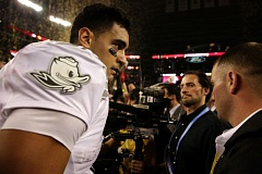 Photo Credit: TRIBUNE PHOTO: JONATHAN HOUSE - Oregon quarterback Marcus Mariota heads off the field after Monday night's national title game.