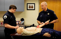 Photo Credit: RAY HUGHEY - Firefighter Damian Peters and Division Chief Tom O'Connor check out the district's new high-tech CPR training mannequinn. The Canby Fire District is now employing a new high performance CPR method aimed at increaseing cardiac arrest survival rates.
