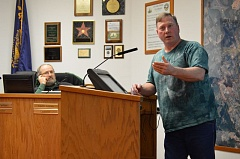 Photo Credit: MARK MILLER - Dennis Sullivan (foreground) speaks in opposition to new restrictions on tobacco use at a public forum in St. Helens City Hall on Wednesday, Jan. 21, as City Councilor Keith Locke listens.