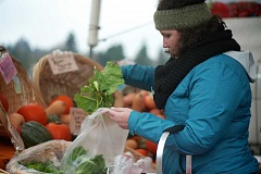 CONNECTION PHOTO: KELSEY OHALLORAN - Hillsdale Farmers Market volunteer Rachel Williams bags fresh produce at the Jan. 11 market.