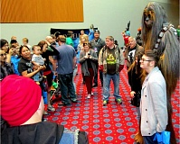 Photo Credit: TRIBUNE PHOTO: KEVIN L. HARDEN - An actor on stilts posed as a 9-foot Wookie with passersby just outside the Oregon Convention Center entrance to the Wizard World Comic Con Saturday afternoon.