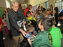 Photo Credit: REVIEW PHOTO: VERN UYETAKE - Rotarian Ted Ricks hands out dictionaries to eager Oak Creek Elementary School students.