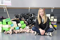Photo Credit: SUBMITTED PHOTO: GABRIELLE WILLIAMS - Matigan Williams proudly sits beside the 215 pairs of dancing shoes she delivered to The Aspire Project in November. Another big delivery is being planned for this spring.