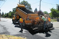 Photo Credit: COLUMBIA COUNTY ROAD DEPARTMENT PHOTO - Columbia County Road Department employees Jeremy Tull and Kelley Lungberg pave a street in an unincorporated area on a summer day in 2014. The county estimates it would need millions more in revenue each year to properly maintain infrastructure.
