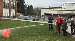 Photo Credit: CONTRIBUTED PHOTO - Students practice their firefighter aim as they shoot water at stacked cones during the lunch with a firefighter Fun with PAWS activity at Sandy Grade.