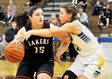 Photo Credit: SETH GORDON - Pick pocket - Savannah Milroy attempts to extract the ball from the hands of Lake Oswego guard Gabby Bruno during Newberg's 57-50 win Feb. 19.